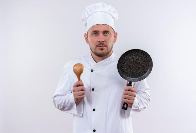 Ernsthaft aussehender junger hübscher koch in der kochuniform, die löffel und bratpfanne hält, die auf lokalisierten weißen raum suchen