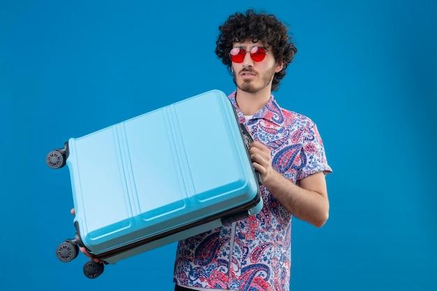 Ernsthaft aussehender junger hübscher lockiger mann, der sonnenbrillen hält, die koffer auf isoliertem blauem raum mit kopienraum halten