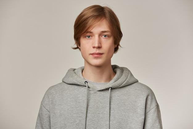 Ernsthaft aussehender männlicher, gutaussehender mann mit blonden haaren. grauen hoodie tragen. menschen- und emotionskonzept. selbstbewusst isoliert über graue wand beobachten