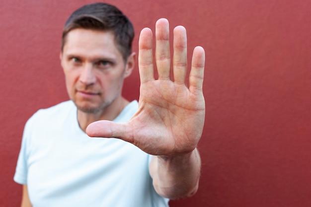 Ernsthaft aussehender mann, der die hand hebt, um zu sagen, hör auf, die stirn zu runzeln, warnen, stimme mit der person nicht überein
