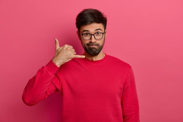 Ernsthaft aussehender unrasierter europäischer mann macht rückruf geste, bleibt immer in kontakt, trägt transparente brille und roten pullover, fragt nach telefonnummer, isoliert auf rosa wand.