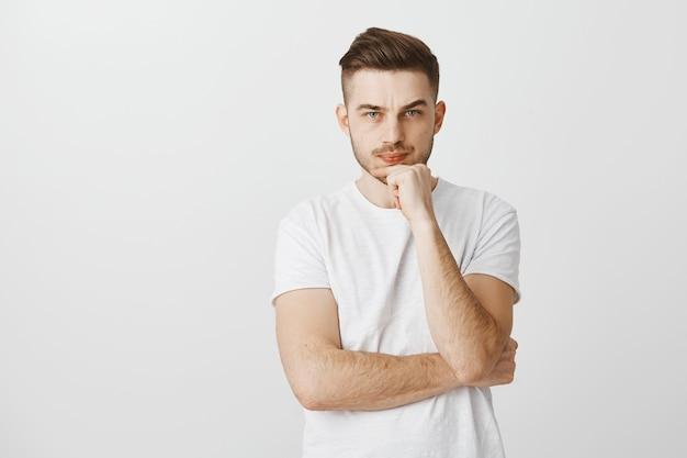Ernsthaft aussehender verwirrter junger mann, der wichtige entscheidung trifft