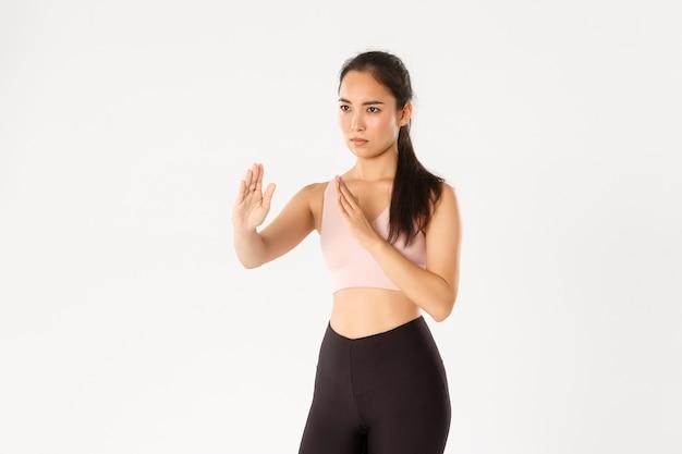 Ernsthaft aussehendes asiatisches mädchen, das zu selbstverteidigungskursen geht, im kampf steht, kampfkunst-pose, aktivkleidung für das training trägt