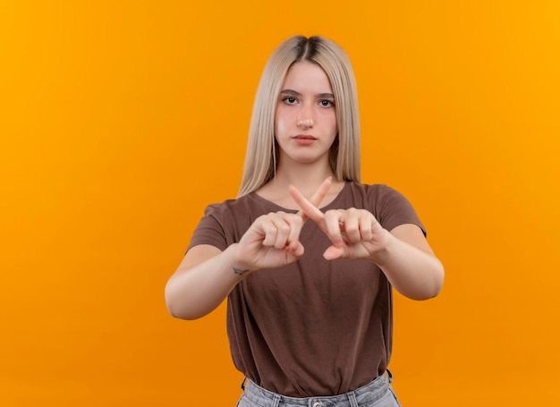 Ernsthaft aussehendes junges blondes mädchen, das nein auf isoliertem orange raum mit kopienraum gestikuliert