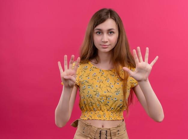 Ernsthaft aussehendes junges mädchen, das vier und fünf auf isoliertem rosa raum mit kopienraum zeigt