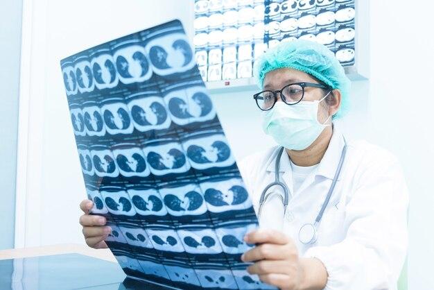Ernsthaft doktor, der geduldigen ct-scan-gehirnfilm vor chirurgiebehandlung hält und schaut