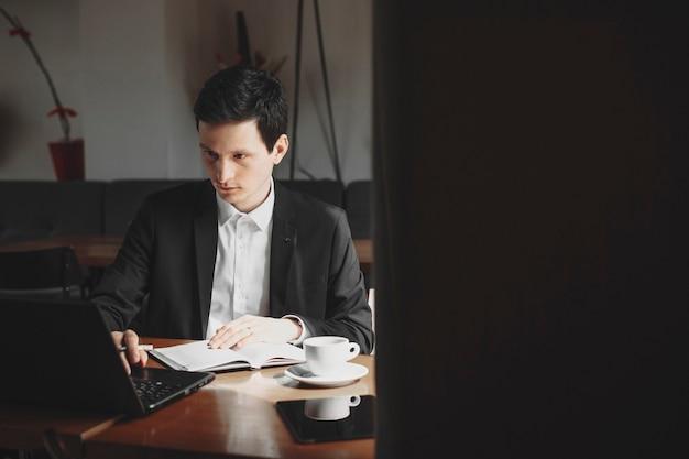 Ernsthaft erwachsener geschäftsmann im anzug, der auf einem notizbuch arbeitet, während er eine tasse kaffee in einem café trinkt.