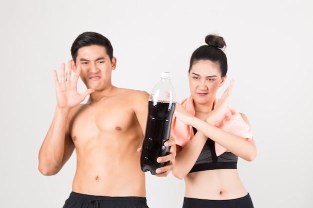 Ernsthaft junger fitnessmann und seine freundin trinken kein cola-wasser. eignung und gesundes lebensstilkonzept. atelieraufnahme auf weißem hintergrund.