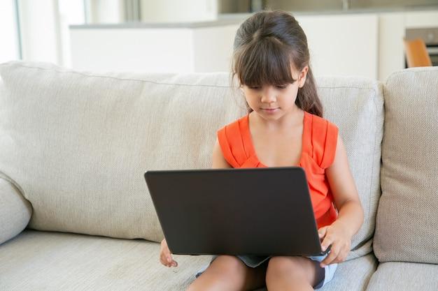 Ernsthaft konzentriertes schwarzhaariges kleines mädchen, das laptop alleine benutzt. nettes kind, das auf sofa sitzt und cartoons auf pc beobachtet.
