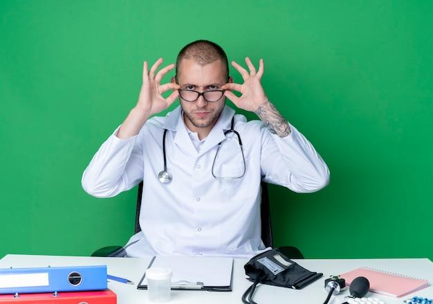 Ernsthaft schauender junger männlicher arzt, der medizinische robe und stethoskop trägt, sitzt am schreibtisch mit arbeitswerkzeugen, die brille tragen und halten, die front lokal auf grüner wand betrachten