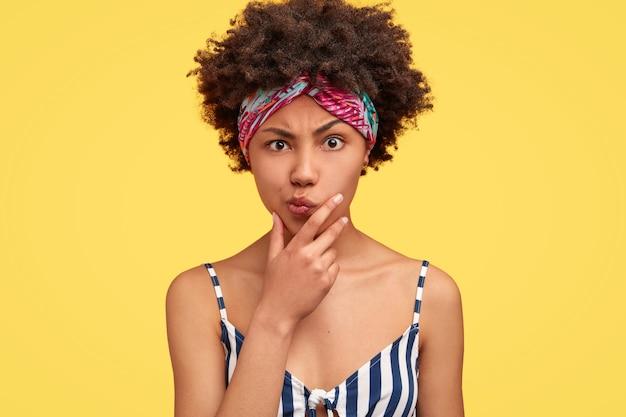 Ernsthaft unzufriedene frau mit afro lockiger frisur, hält kinn, runzelt die stirn, gekleidet in gestreifte kleidung