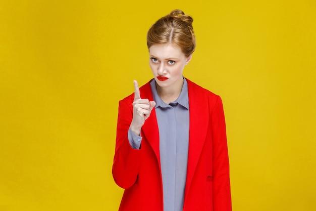 Ernsthaft wütende frau im roten anzug macht dich aufmerksam