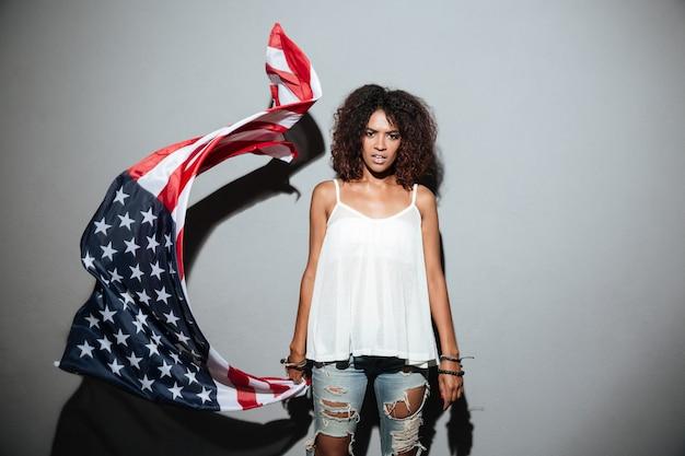 Ernsthafte afrikanische frau, die mit amerikanischer flagge steht und winkt