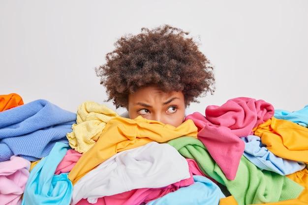 Ernsthafte afro-amerikanerin posiert in der nähe eines haufens bunter, unsortierter kleidung, nachdem das waschen ordnung im schrank gebracht hat, schaut aufmerksam weg, isoliert über weißer wand, sammelt kleidung zum verkauf