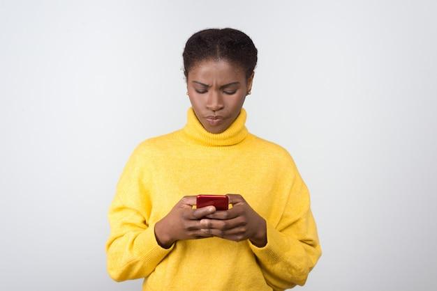 Ernsthafte afroamerikanische frau, die auf smartphone schreibt
