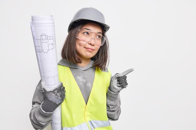 Ernsthafte asiatische architektin trägt schutzhelm-sicherheitskleidung und transparente brillen halten blaupausen, die auf dem kopierraum die richtung zur baustelle zeigen. branchenkonzept