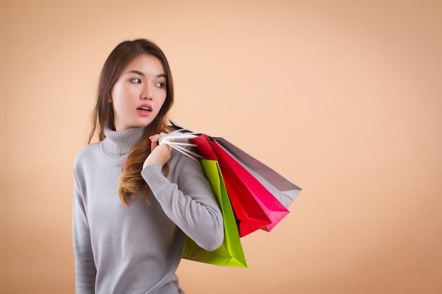 Ernsthafte asiatische frau mit einkaufstüten