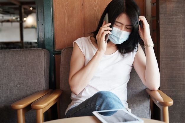 Ernsthafte asiatische geschäftsfrau trägt eine maske, um civid-19 zu verhindern, und ruft im wohnzimmer mit dem smartphone an. gesund und geschäftlich mit technologiekonzept