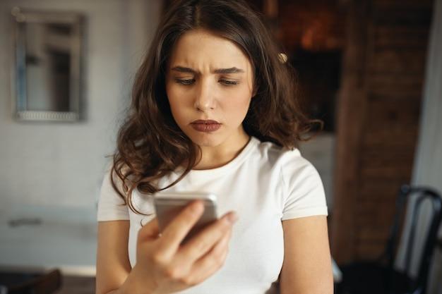 Ernsthafte attraktive junge frau, die smartphone hält und die stirn runzelt und traurige nachrichten liest