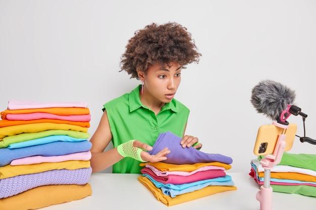 Ernsthafte aufmerksame junge afro-amerikanerin spricht mit anhängern, während sie wäsche faltet, die sich aufmerksam auf die smartphone-kamera konzentriert