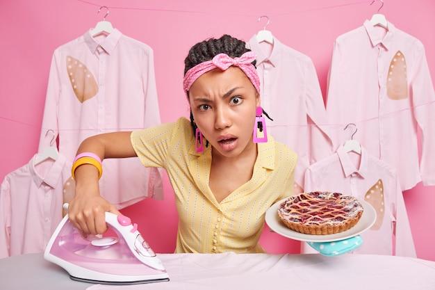 Ernsthafte aufmerksame junge hausfrau, die sich direkt auf die kamera konzentriert, verwendet elektrisches bügeleisen, um die wäsche zu streicheln, die damit beschäftigt ist, köstlichen kuchen für die familie zu kochen, trägt stirnband und kleid bei der hausarbeit