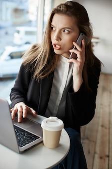 Ernsthafte besorgte europäische frau, die im café sitzt, kaffee trinkt und mit laptop arbeitet, auf smartphone spricht, während sie ängstlich beiseite schaut