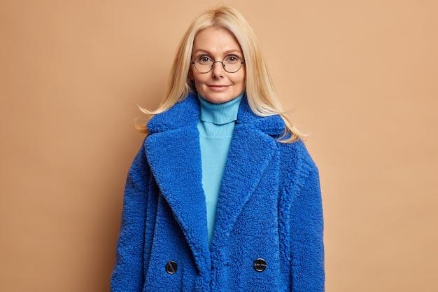 Ernsthafte blonde frau im blauen pelzmantel sieht mit charmantem ausdruck direkt zufrieden aus, nachdem sie einkaufen gegangen ist und modische winteroberbekleidung gekauft hat.