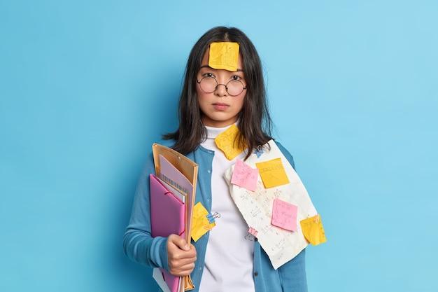 Ernsthafte brünette asiatische frau mit aufkleber auf der stirn klebt beschäftigt papierkram bereitet finanzbericht trägt runde brille lässig pullover hat klugen blick.