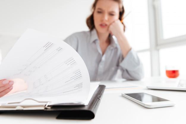 Ernsthafte brünette frau, die papiere liest, während sie am arbeitsplatz in leichter wohnung sitzt, selektiver fokus auf dokument