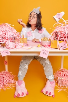 Ernsthafte büroangestellte in pyjama und schlafmaske auf der stirn schaut aufmerksam auf die nägel und arbeitet als freiberuflerin von zu hause aus, die auf dem desktop mit rosa geschnittenem papier frühstücken geht