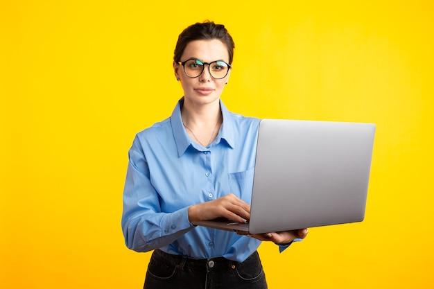 Ernsthafte bürofrau in shurt in gläsern, die laptop halten und ihn verwenden, der lokal über dem gelben hintergrund steht.