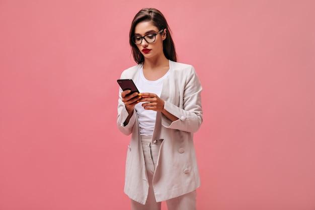 Ernsthafte dame in brille und anzug, die am telefon plaudert. schöne brünette mit roten lippen im beige anzug hält smartphone auf lokalisiertem hintergrund.