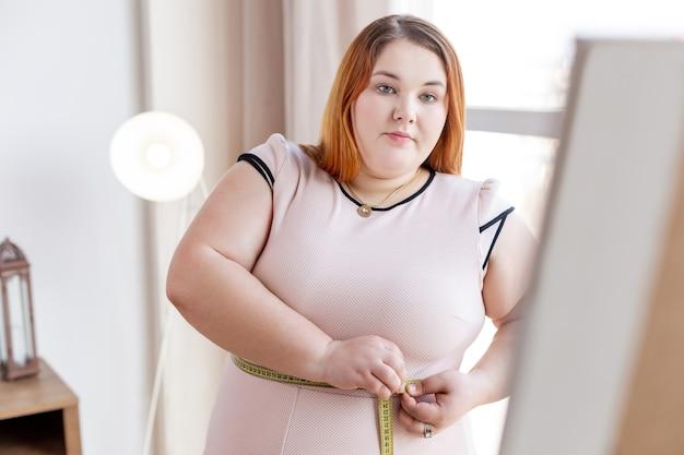 Ernsthafte dicke frau, die über ihr gewicht nachdenkt, während sie schön aussehen möchte