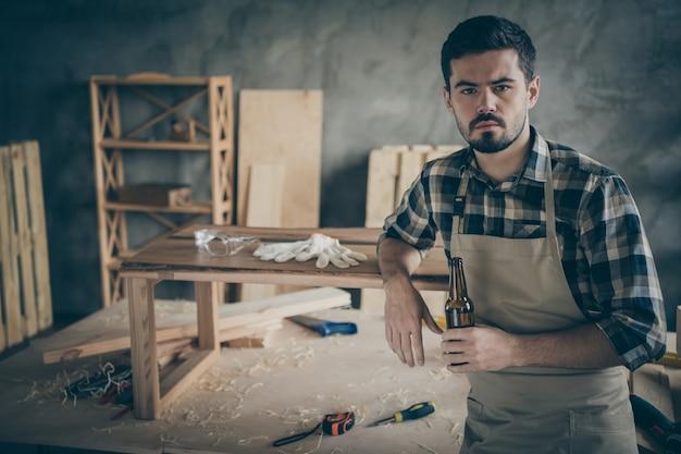 Ernsthafte erfolgreiche arbeiter hartholz unternehmer getan seine platte tisch restaurierungsarbeiten haben ruhe entspannen halten glasflasche bier in der garage des hauses zu hause halten