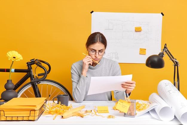 Ernsthafte erfolgreiche, erfahrene designerin erstellt neue architektenskizzen, die aufmerksam in papierposen auf dem desktop konzentriert sind, umgeben von blaupausen, bereitet sich auf die vorstandssitzung mit kollegen vor
