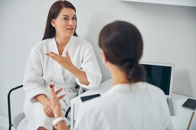 Ernsthafte erwachsene frau im bademantel, die sich bei einem qualifizierten dermatologen über ihre hautprobleme beschwert