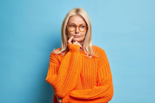 Ernsthafte europäische frau sieht nachdenklich aus und denkt, die idee entscheidet über etwas, das zweifel an einem orangefarbenen strickpullover hat.