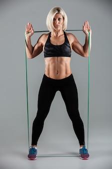Ernsthafte fitnessfrau, die mit elastischem gummi streckt