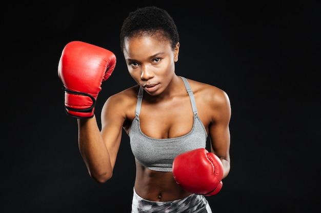 Ernsthafte fitnessfrau in boxhandschuhen, die auf die schwarze wand schaut