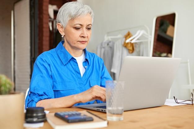 Ernsthafte fokussierte hausfrau mittleren alters, gekleidet in blaues hemdtastatur auf tragbarem computer, der strom-, gas- und stromrechnungen online zahlt und am schreibtisch mit taschenrechner sitzt. selektiver fokus