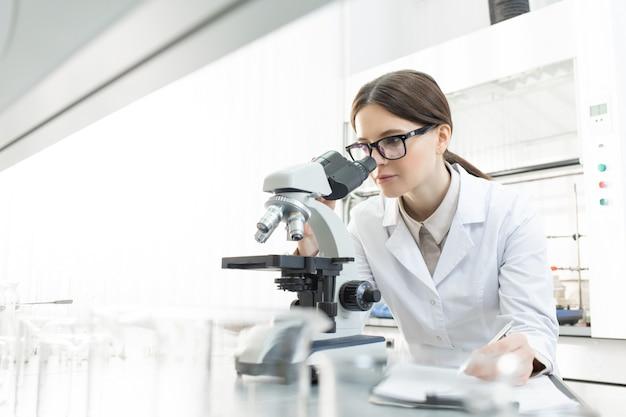 Ernsthafte forscherin im weißmantel, die am arbeitsplatz im mikroskop schaut, während sie die merkmale von covid19 im wissenschaftlichen labor untersucht