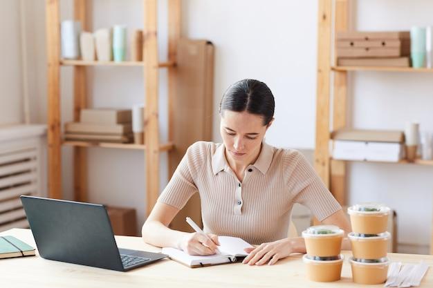 Ernsthafte frau, die am tisch sitzt und sich auf ihre arbeit konzentriert, macht sich notizen im notizblock und registriert die lieferung von lebensmitteln