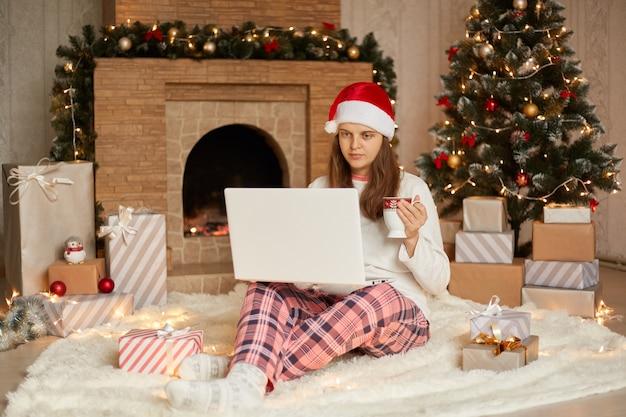 Ernsthafte frau, die videoanruf über laptop hat, mit jemandem spricht oder online arbeitet, weihnachtsferien zu hause, dame, die weißen lässigen pullover, karierte hosen und weihnachtsmütze trägt, heißen heißen tee trinkt.