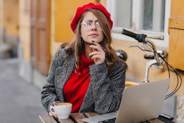 Ernsthafte frau mit elegantem lockigem haar, das zur kamera schaut, während mit computer im straßencafé arbeitet