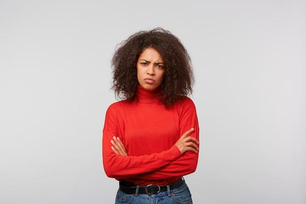 Ernsthafte frau mit lockigem afro-haar, die mit gekreuzten händen steht und die stirn runzelt
