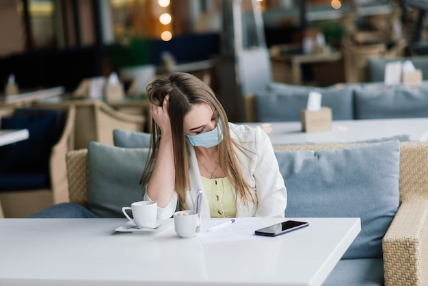 Ernsthafte frau mit schützender gesichtsmaske, die die nachrichten des smartphones auf einer caféterrasse prüft