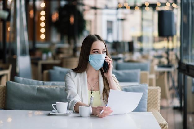 Ernsthafte frau mit schützender gesichtsmaske, die nachrichten auf einer caféterrasse prüft