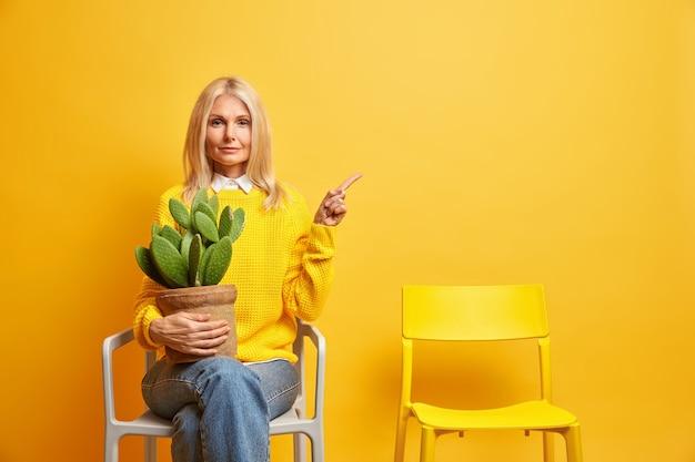Ernsthafte frau mittleren alters posiert mit kaktus am stuhl und sieht selbstbewusst aus und zeigt auf den kopierraum
