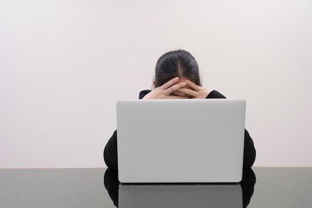 Ernsthafte frau packte ihren kopf mit gestresstem vor laptop