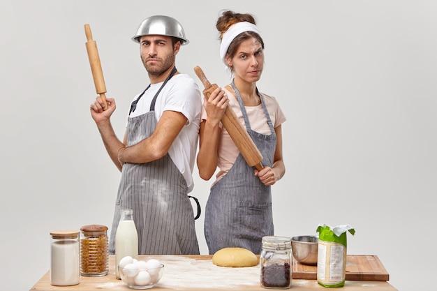 Ernsthafte frauen- und männerköche treten zurück, halten nudelhölzer, nehmen an kulinarischen kämpfen teil und demonstrieren kochkünste in der nähe des tisches mit zutaten in der küche. wir regieren in der kulinarischen welt